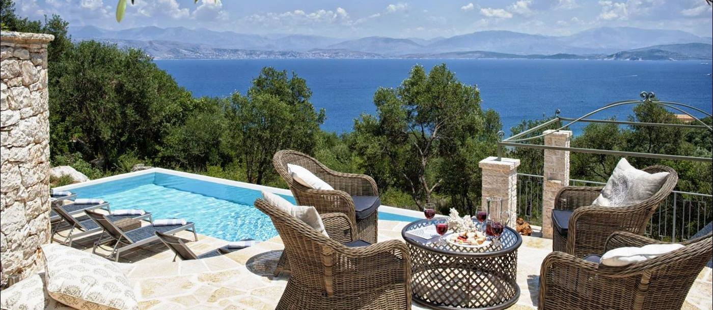 sun terrace with 4 wicker chairs and a table overlooking the pool with views of the sea at villa apraos in corfu, Greece