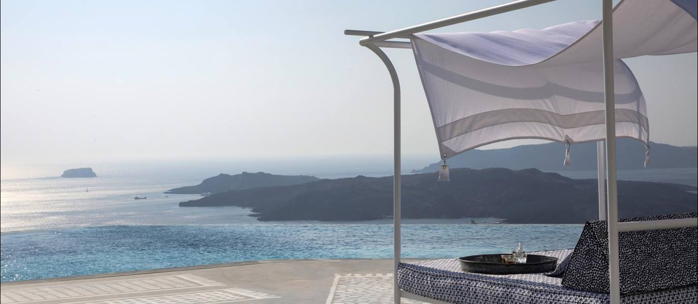 Day bed with sea view on terrace by infinity pool at Erosantorini on Santorini, Greece