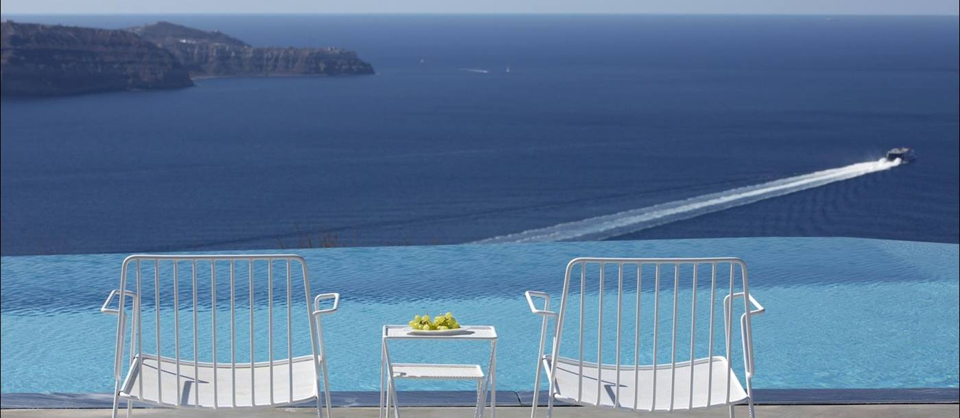 Chairs and coffee next to infinity pool on terrace with sea view at Erosantorini on Santorini, Greece