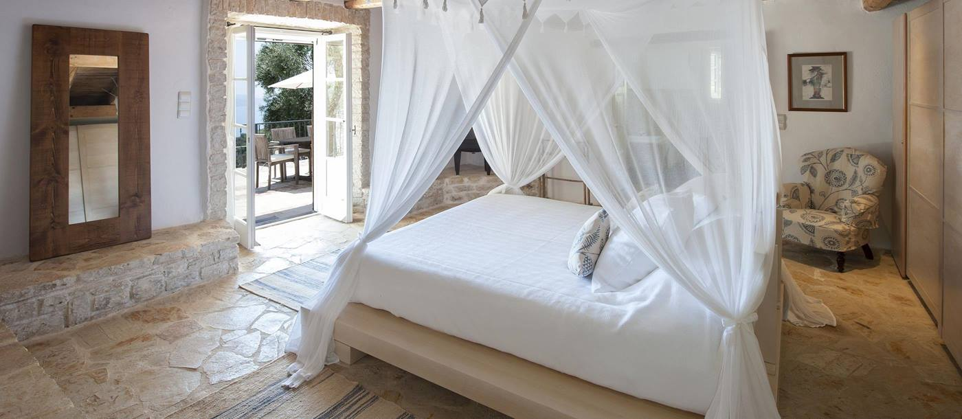 A double bedroom with mosquito net in Morus, Greece