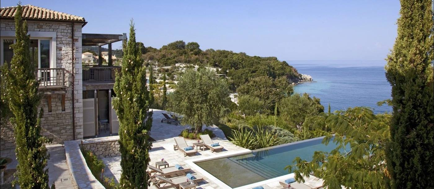 View of villa with patio, sun loungers, towels, pool, trees and sea view at the Odysseus Estate on Corfu, Greece
