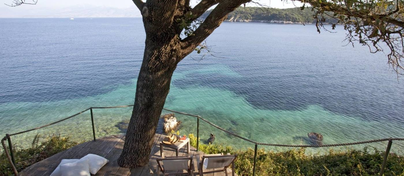 Beach side balcony with deck chairs, coffee table, cushions, tree and sea view at the Odysseus Estate on Corfu, Greece