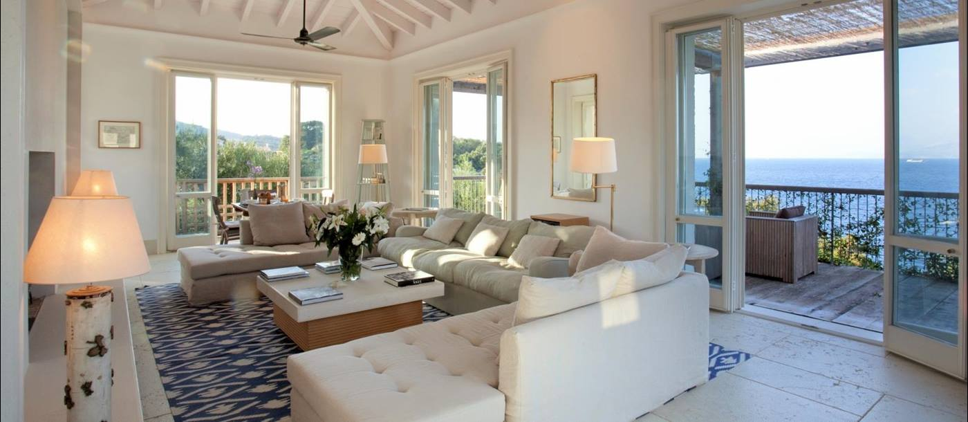 Living room with sofas, coffee table, flowers, lamps, fans, French doors and sea view at the Odysseus Estate on Corfu, Greece