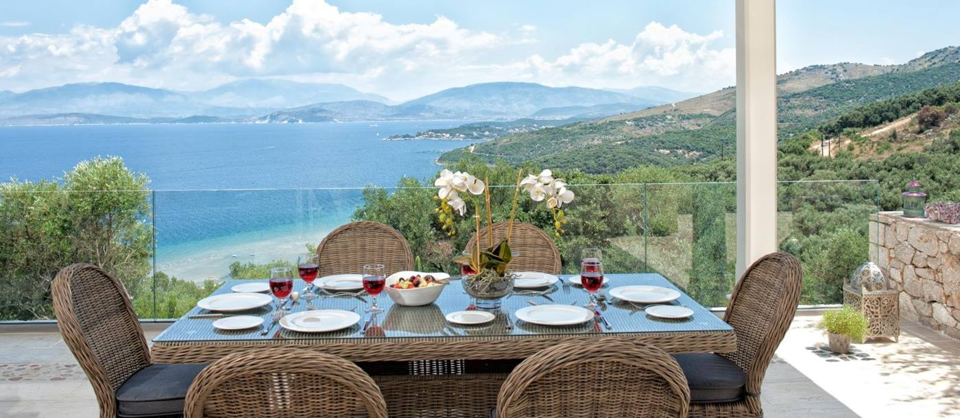 Outdoor dining table set for lunch with view towards the sea at Villa Dionysos, Corfu