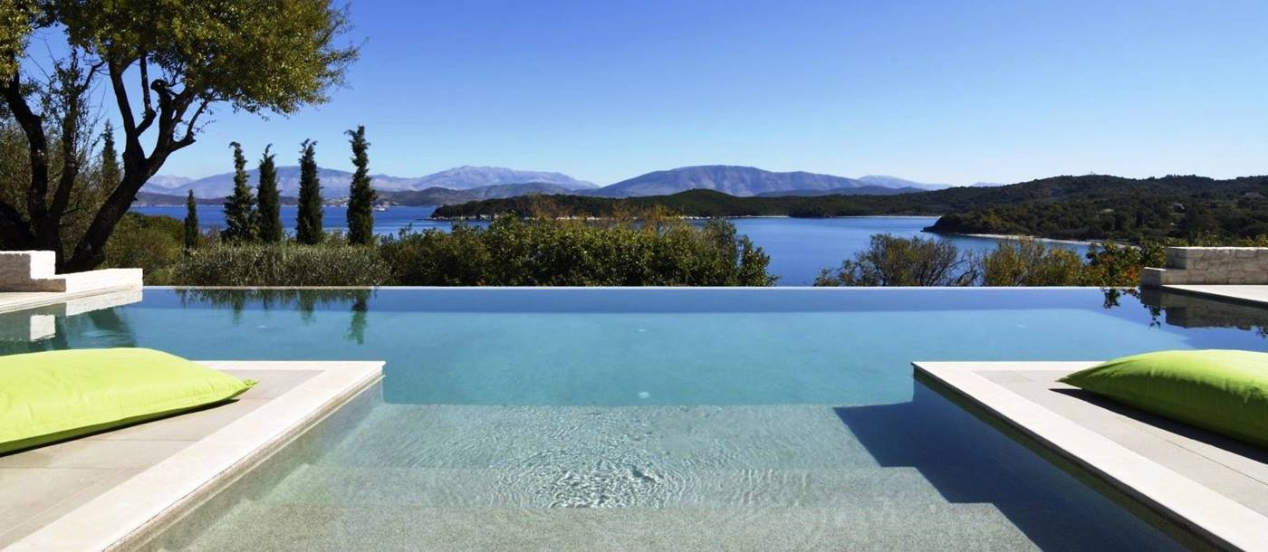 View over the pool with the sea and hills in the background at villa eleni in corfu, Greece