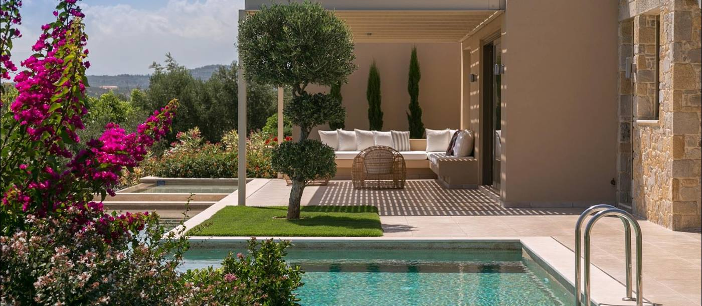 View of pool and outdoor lounge area with comfy chairs and sofa and flowers in foreground at Villa Ianira on Crete, Greece