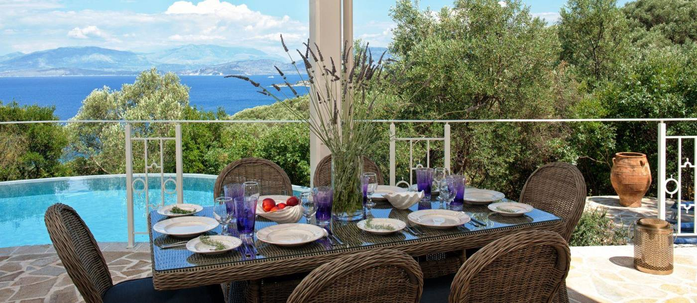 Brown wicker dining table set for dinner and six chairs on the terrace with view of the sea villa kalamaki in corfu, Greece
