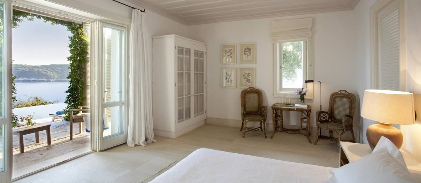 Bedroom with double bed, lamp, table, chairs, art, wardrobe, French doors & sea view at Villa Penelope on Corfu, Greece
