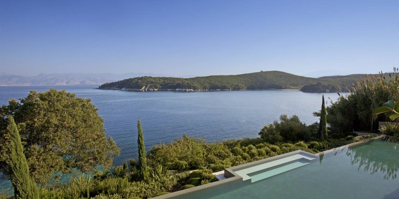 View of pool, trees, plants, sea and nearby headland at Villa Penelope on Corfu, Greece