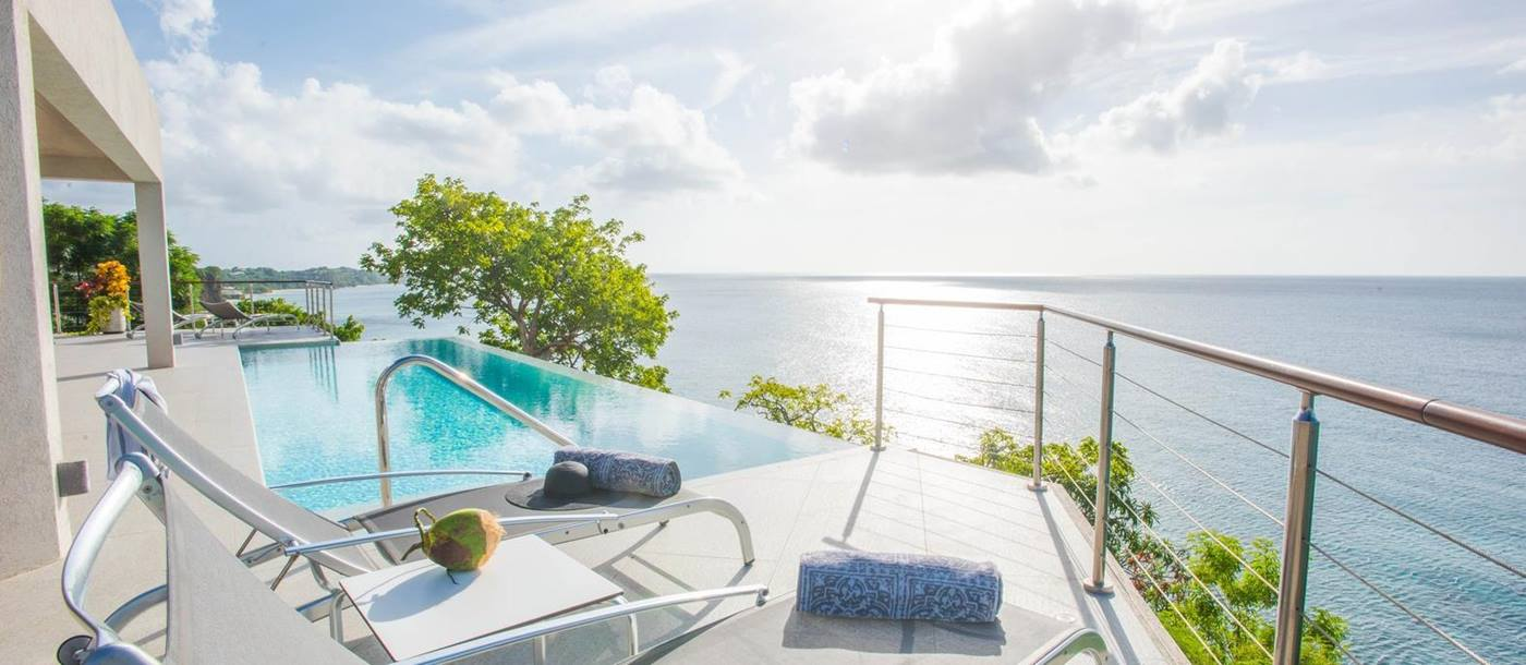 The sundeck with sunloungers and pool at Laluna, Grenada