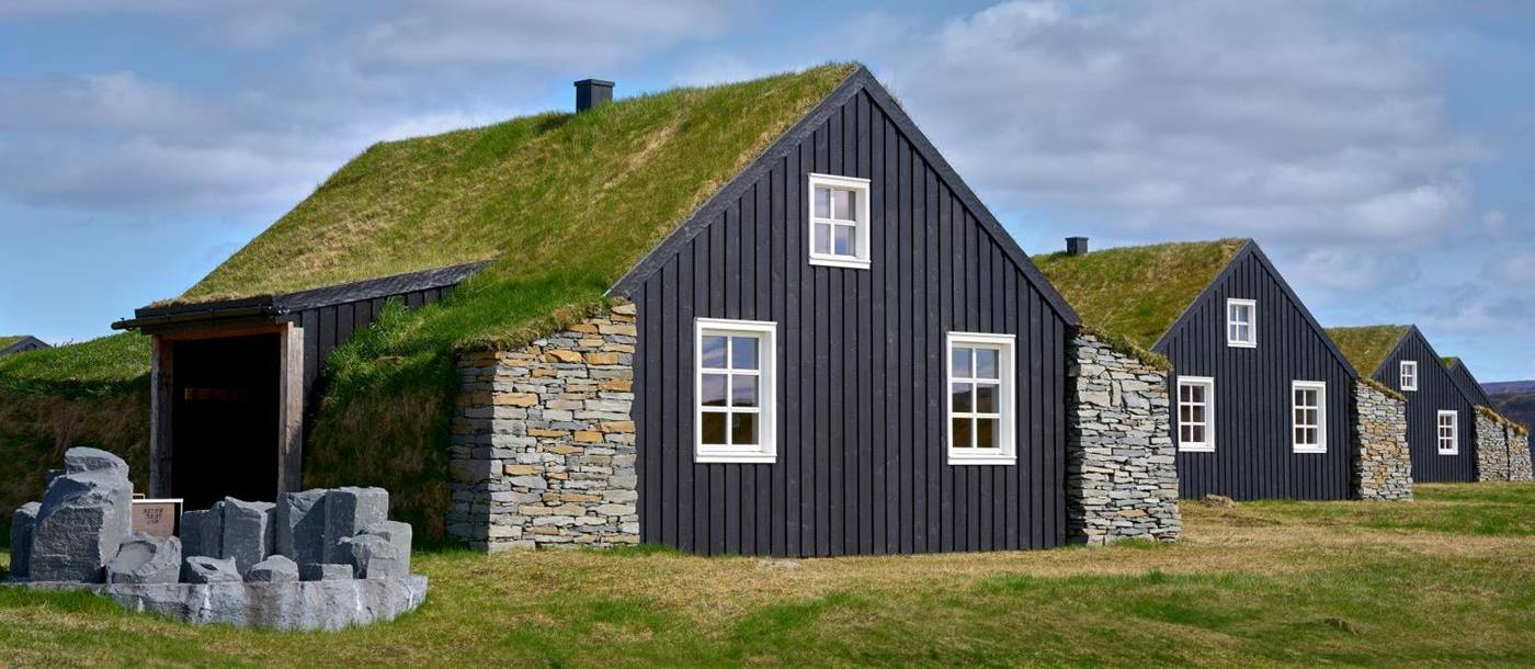 The turf covered roofs of the cottages at Torfhus Retreat hotel in Iceland
