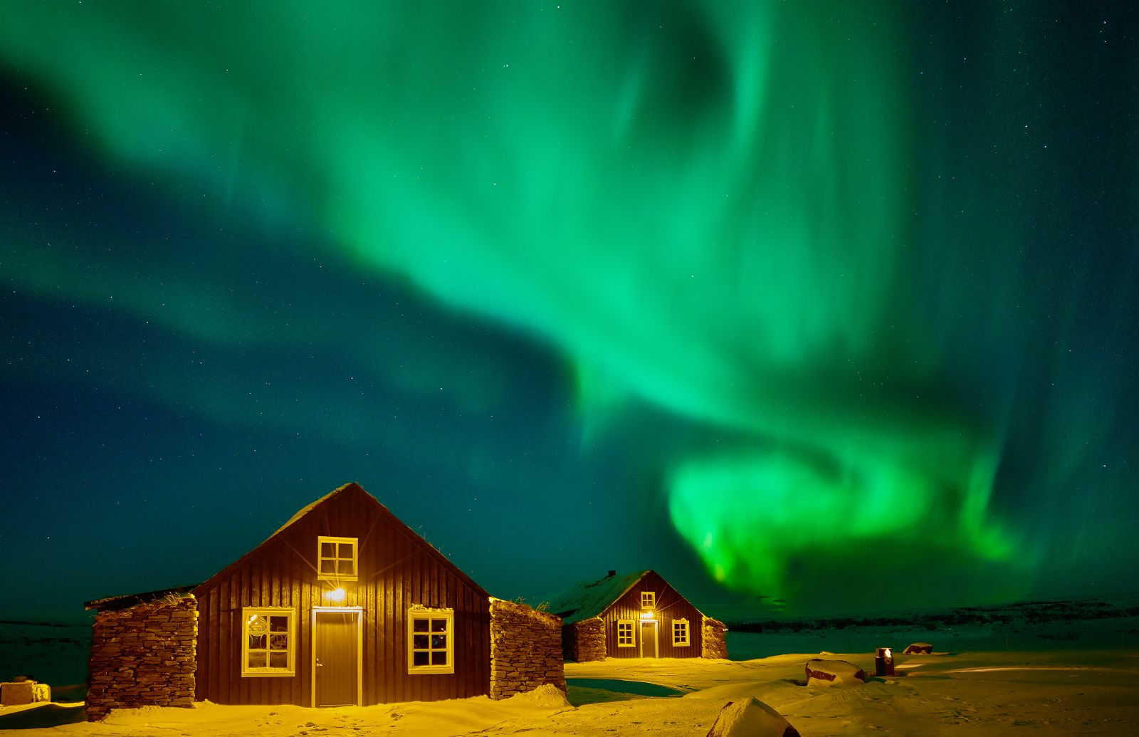 Bright Northern Lights over the Torfhus Retreat hotel in Iceland
