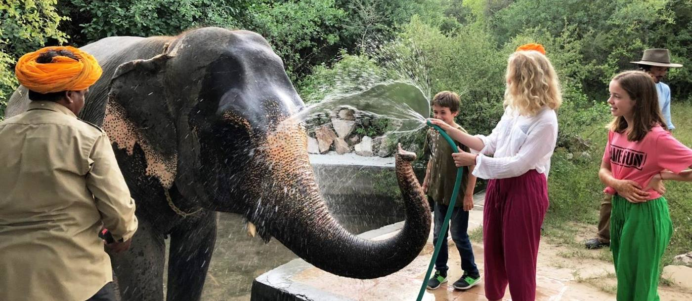 A lady and two children washing an elephant with a hose pipe in India