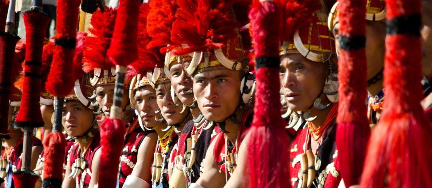 A row of men from the Tribes of Nagaland dressed in traditional red headdress and holding spears at the annual Hornbill Festival in India