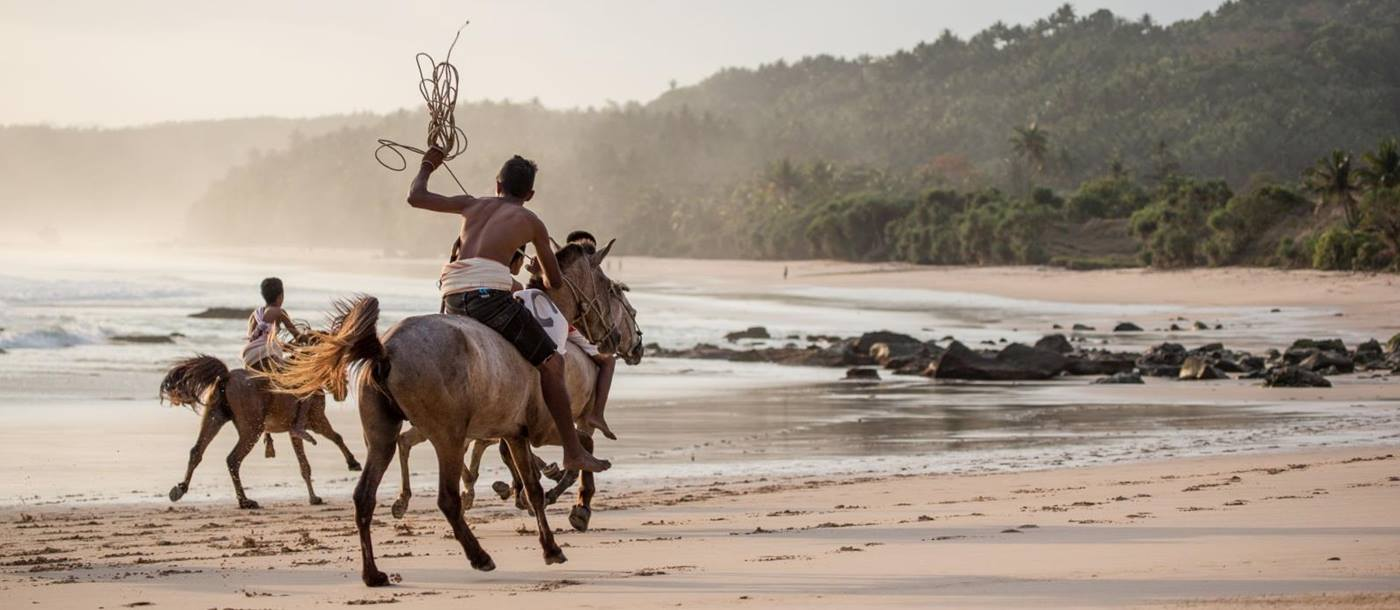 Locals riding subanese stallions on the beach at Nihi Sumba