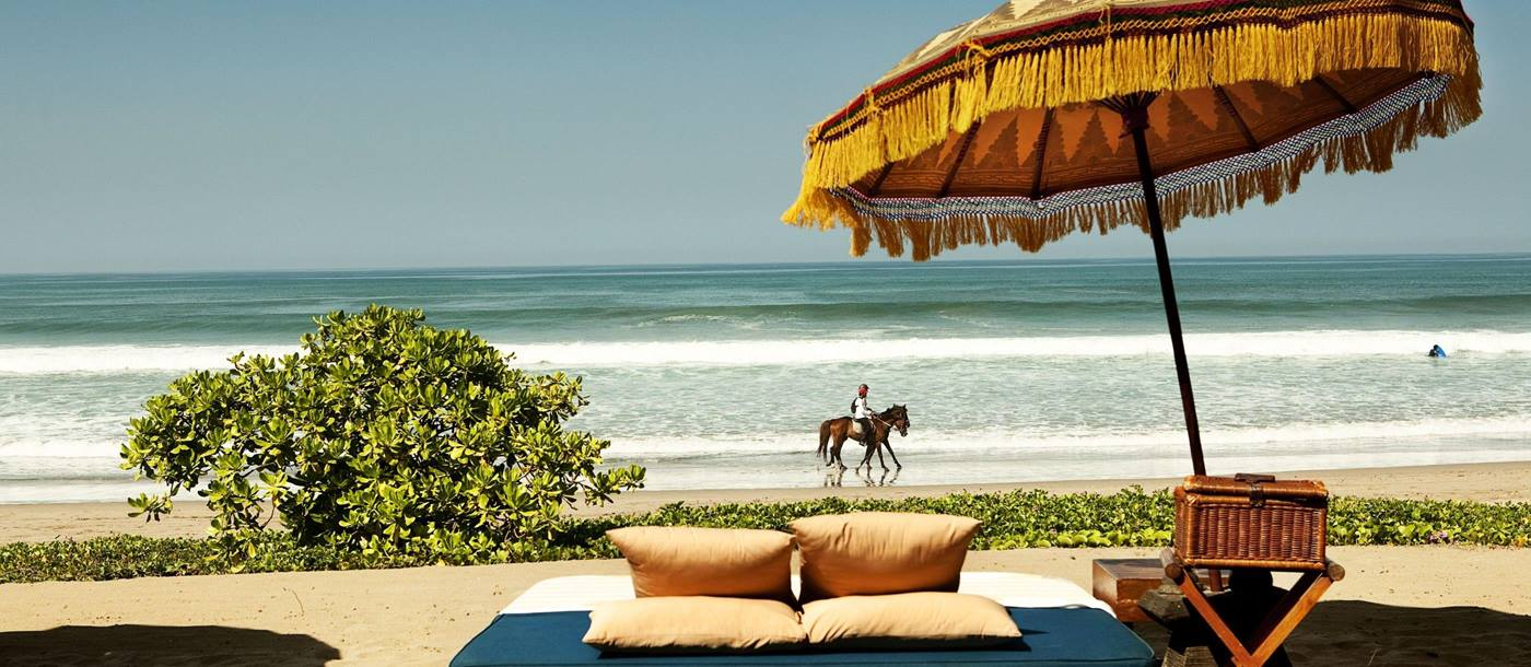 Day bed with horse rider in background at Oberoi Bali, Indonesia