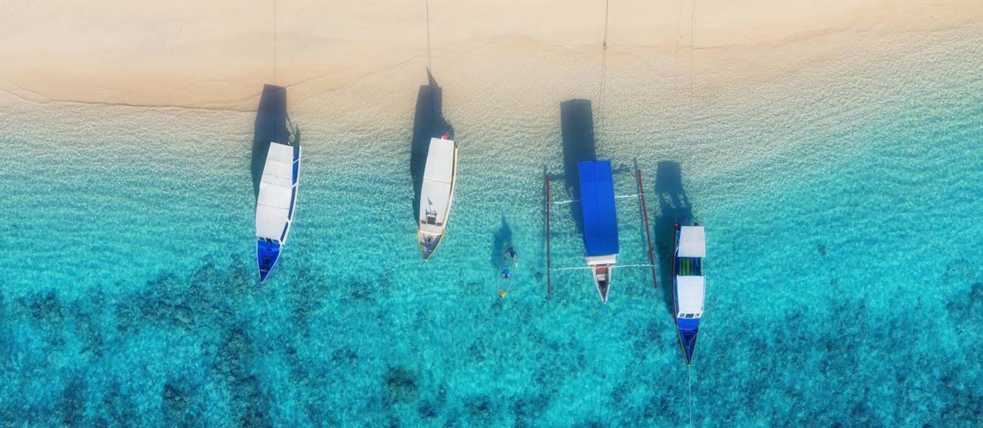 Aerial view of boats on a white sand beach on the Gili Islands in Indonesia