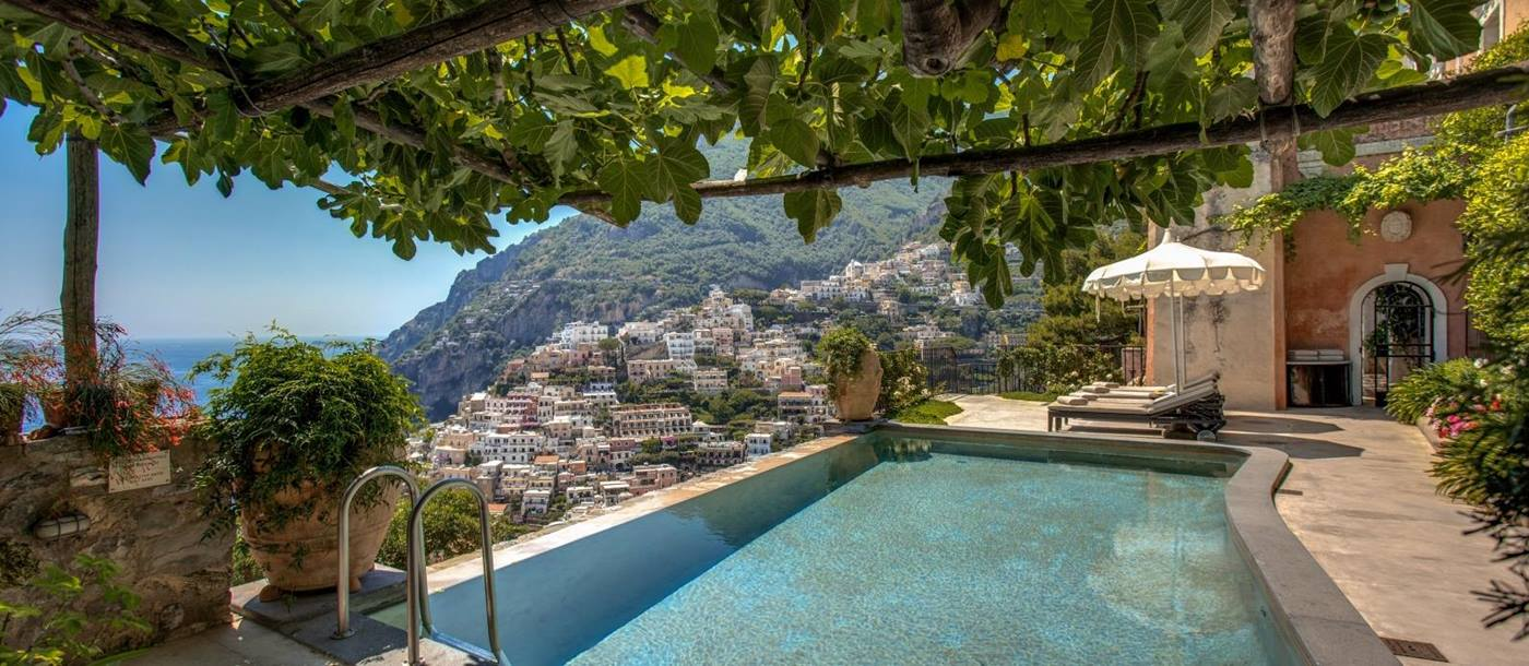 Pool with shaded seating and view towards Amalfi
