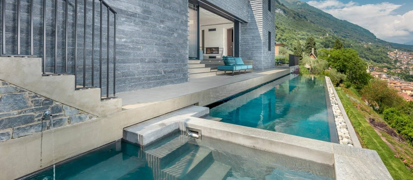 Jacuzzi, infinity pool and back of villa with terrace, sofa and doors to living area at Villa Cielo on Lake Como in Italy