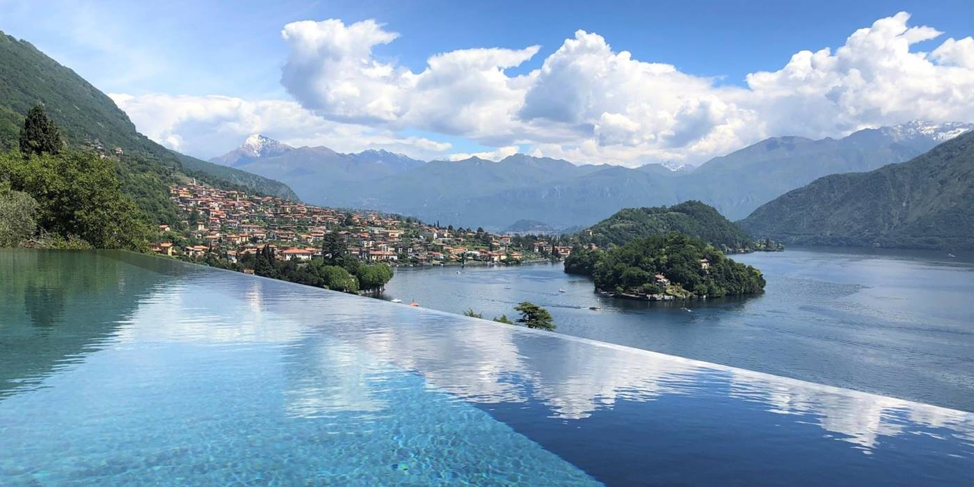 Pool with view of lake, mountains, islands and nearby town at Villa Cielo on Lake Como in Italy
