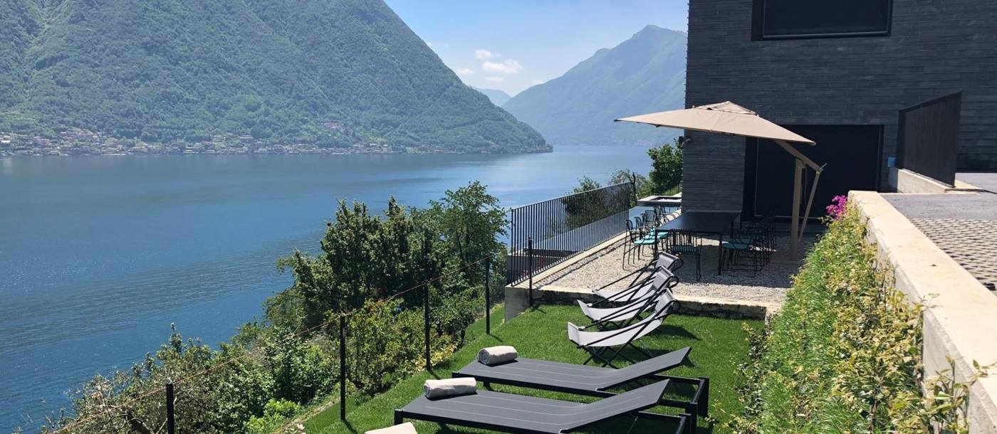 Garden area with sun loungers and patio with dining table, umbrella and view of lake at Villa Cielo on Lake Como in Italy