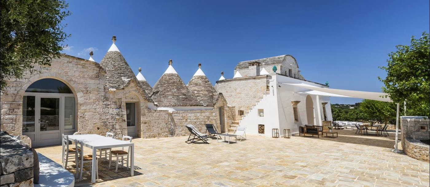 Exterior view of villa and patio with sun loungers, dining tables and chairs at Masseria Bianco in Puglia, Italy