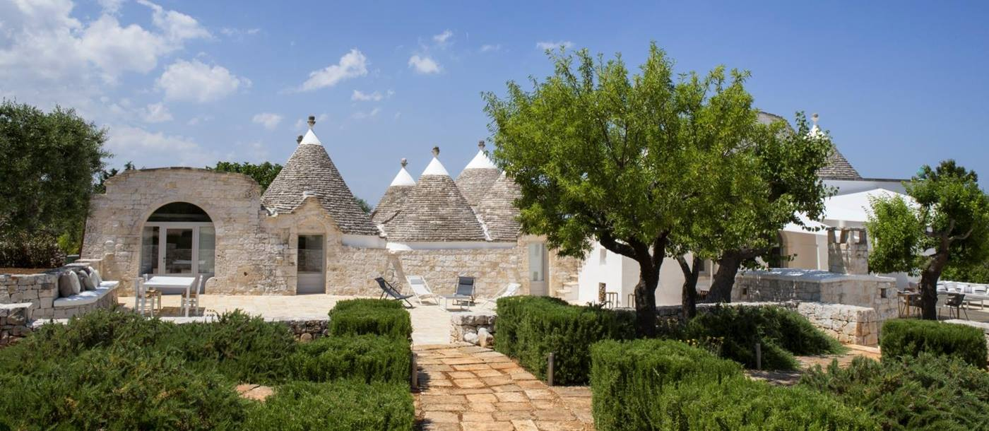 Exterior view of villa and gardens with trees and hedges at Masseria Bianco in Puglia, Italy