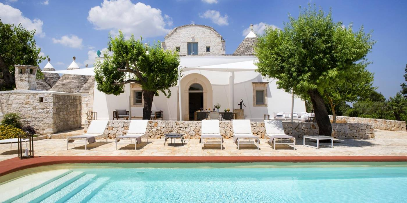 Pool and pool area with sun loungers, coffee table and trees at Masseria Bianco in Puglia, Italy