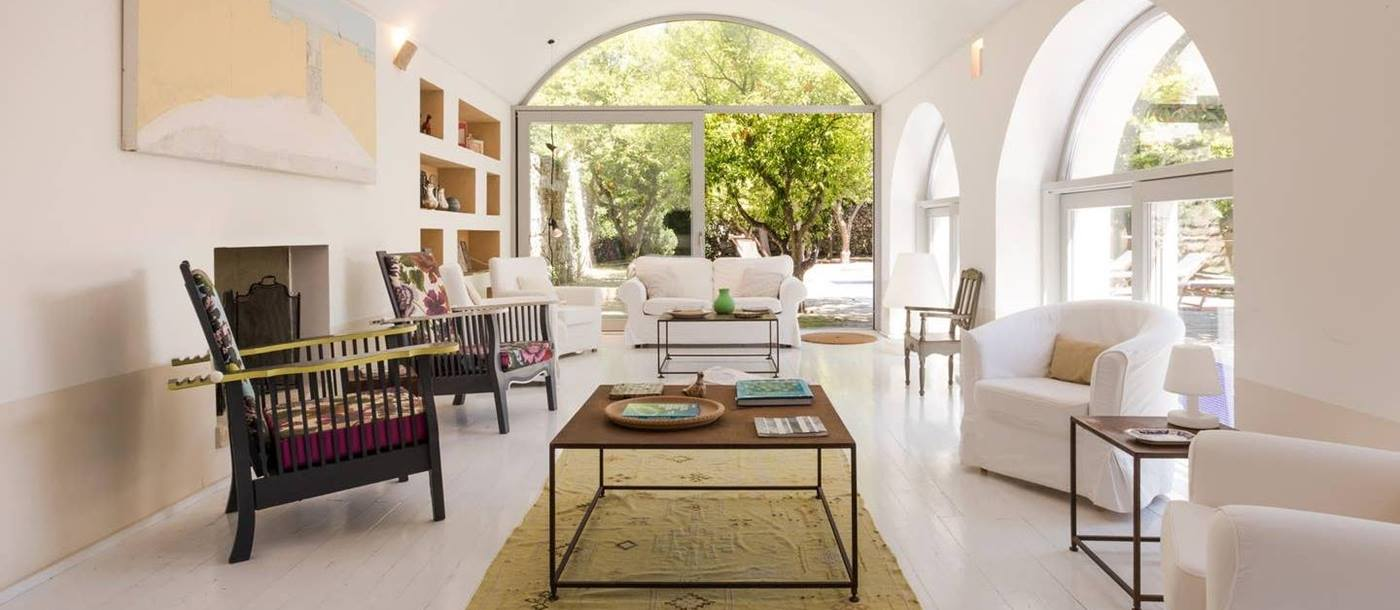 Living room with sofa, 6 armchairs, coffee tables, painting, shelves and patio doors at Palazzo del Duca in Puglia, Italy