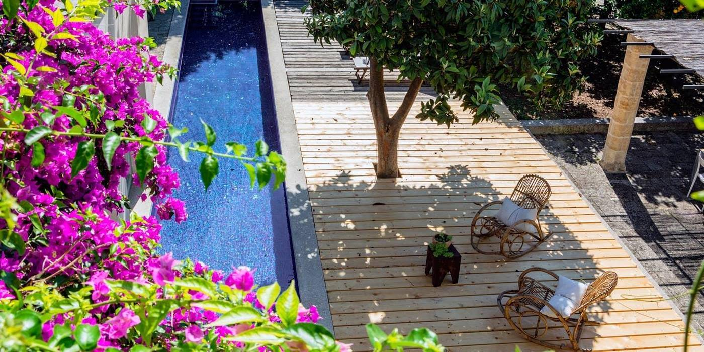 Long swimming pool and decking area with flowers, tree and rocking chairs at Palazzo del Duca in Puglia, Italy