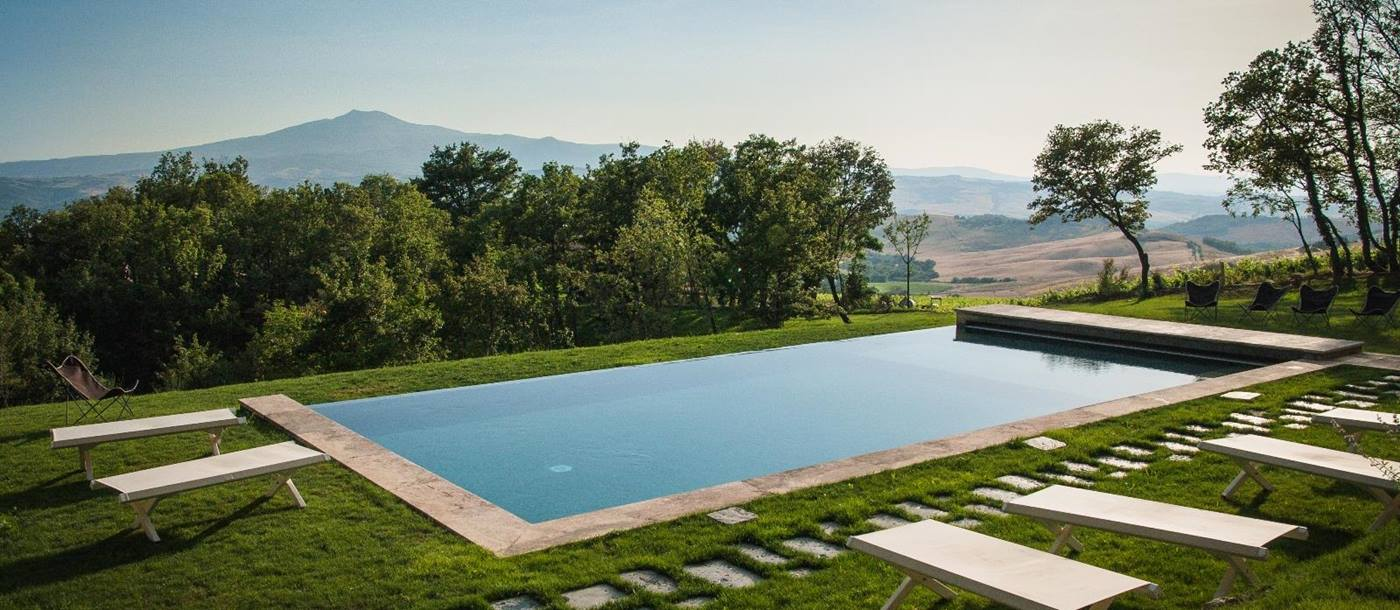 The swimming pool with mountainous backdrop seen from Il Cocceto, Tuscany