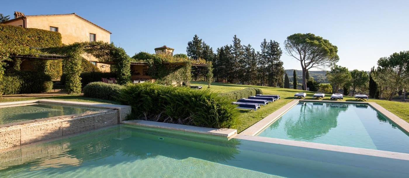 Large swimming pool in garden with sun loungers, grass, hedges & trees at Il Serratone in Tuscany, Italy