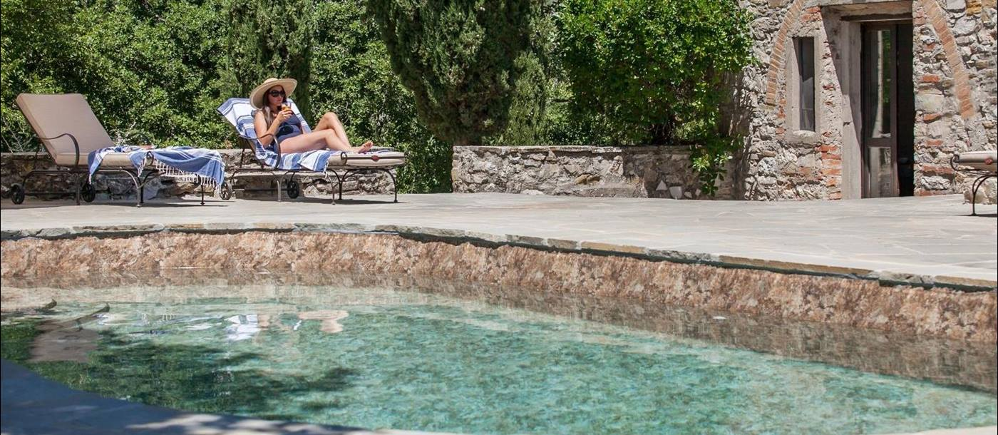 The swimming pool with a woman sunlounging at La Tenuta, Tuscany