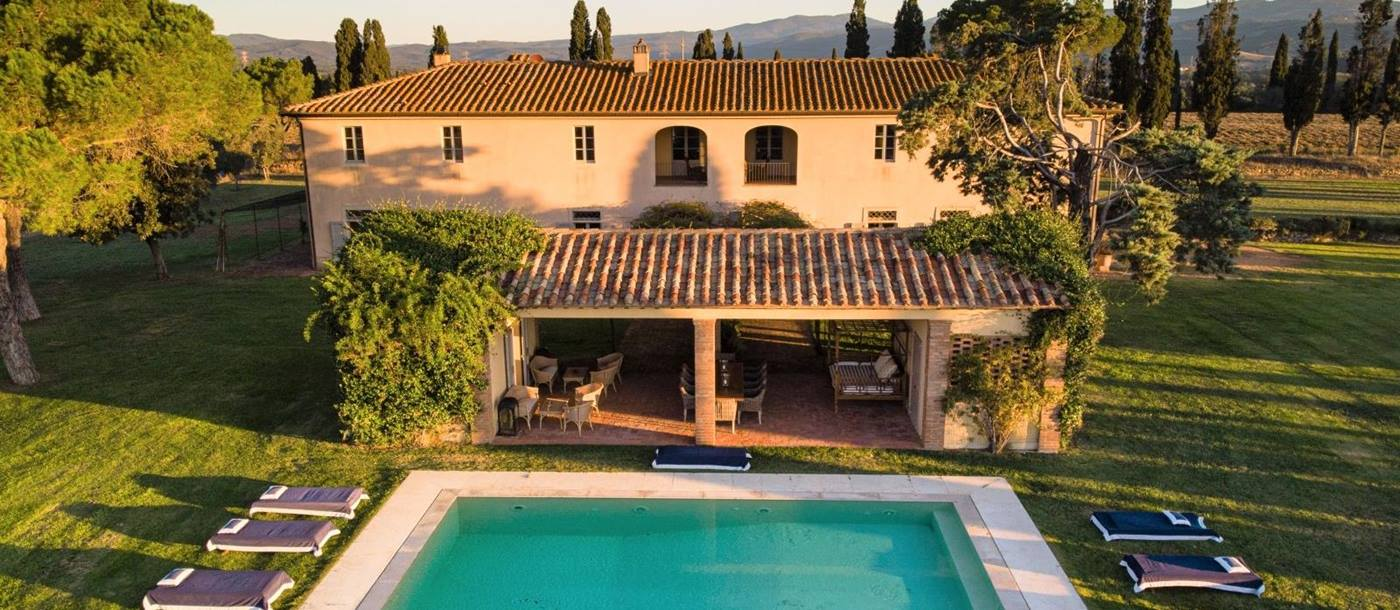 Aerial shot of villa, covered outdoor dining area, garden and pool at La Vigna in Tuscany, Italy