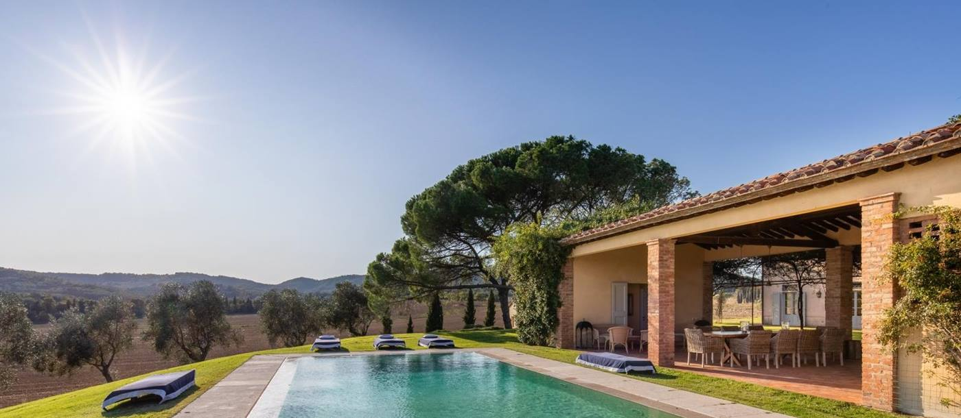 Pool area with sun loungers and covered outdoor dining area in garden at La Vigna in Tuscany, Italy