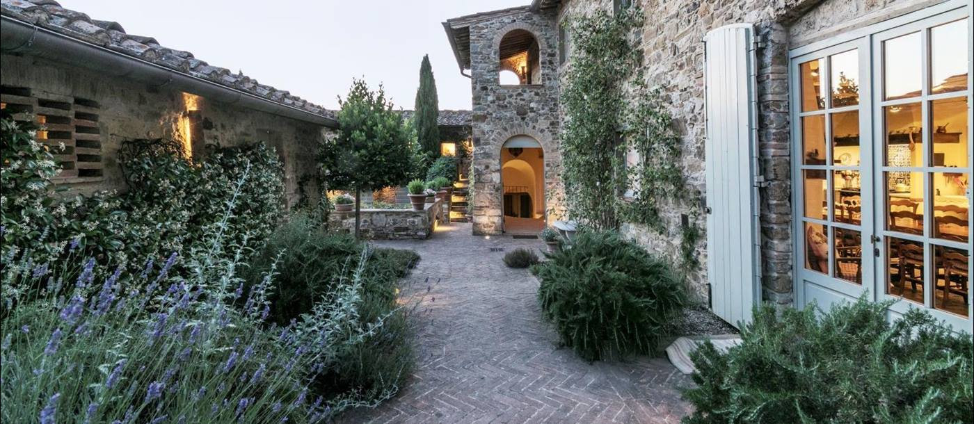 A path lined with lavendar bushes and shrubs in the courtyard at Villa Podere Cipressi in Tuscany