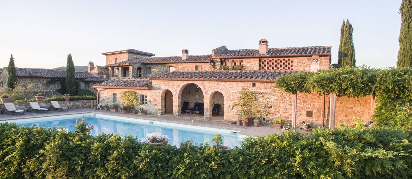 Garden, swimming pool and facade of Podere Cipressi, Tuscany
