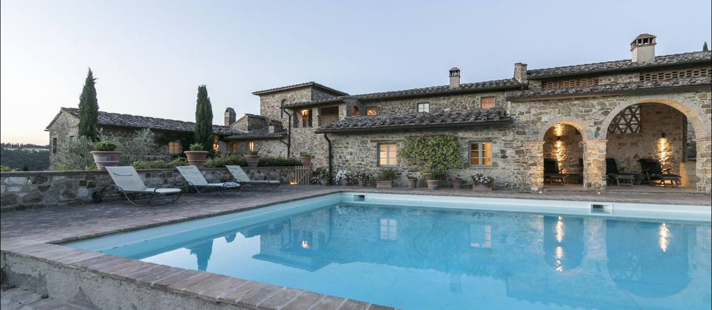 The swimming pool at twilight with the lights on at Villa Podere Cipressi in Tuscany
