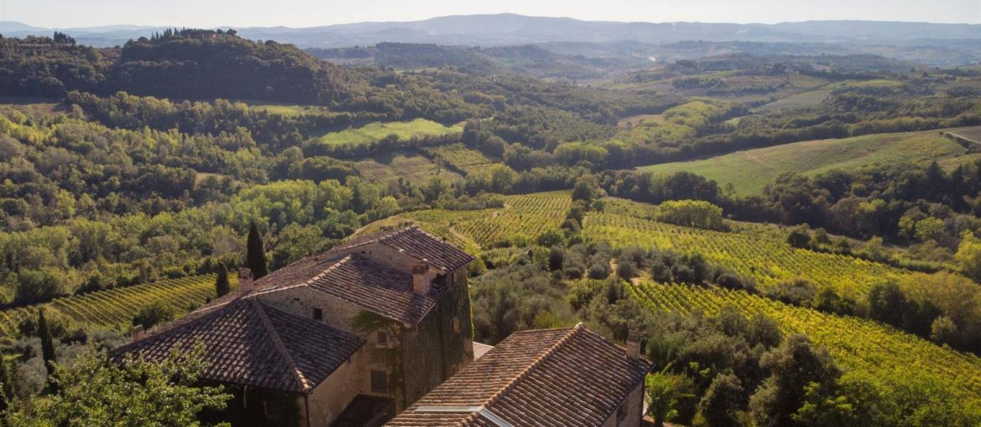 Aerial view of villa, surrounding countryside and hills at Torre del Santo in Tuscany, Italy