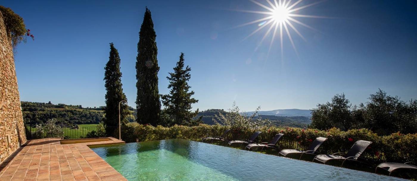 Pool with patio, sun loungers, shower and countryside view at Torre del Santo in Tuscany, Italy