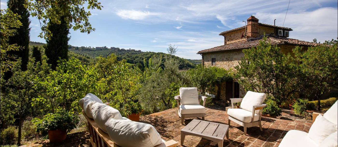 Patio with comfy chairs, coffee table and countryside view at the back of Villa Baciata in Tuscany, Italy