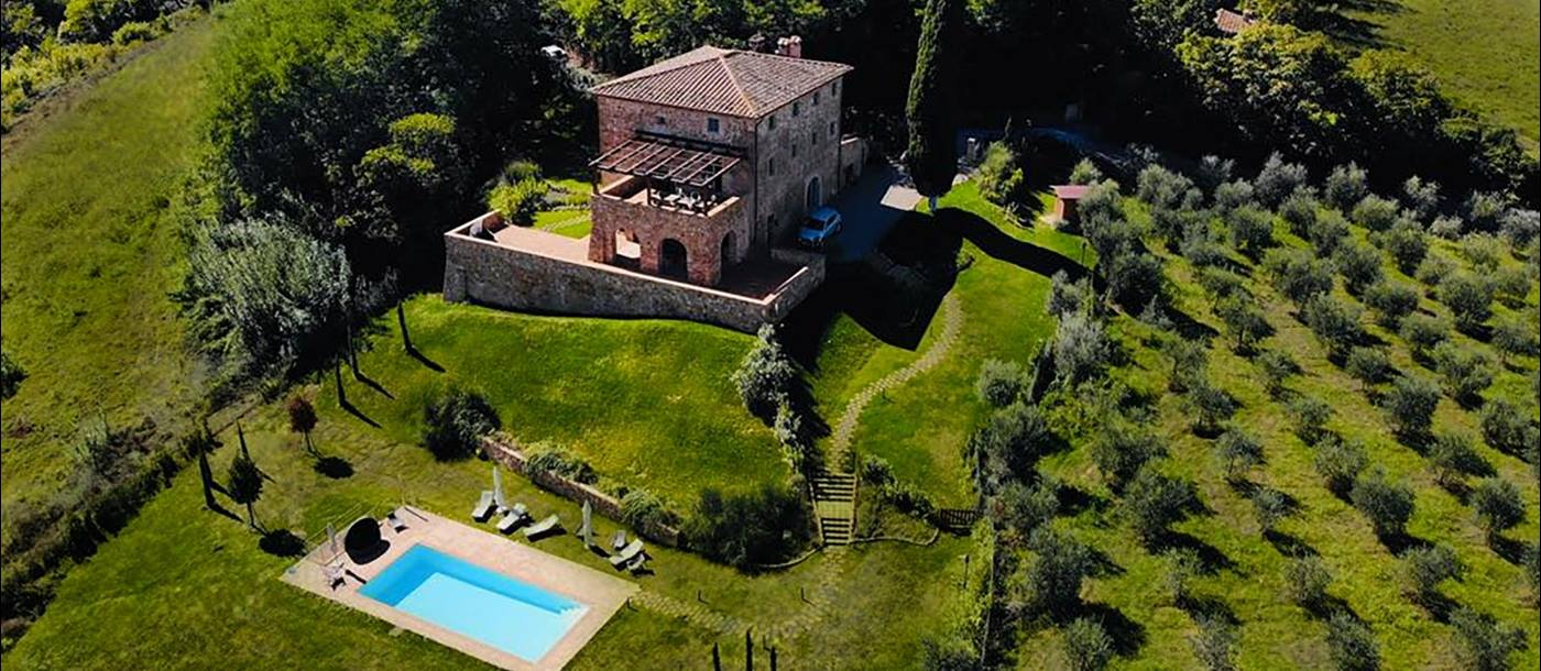 Aerial view of villa and pool with olive groves, green fields and trees at Villa del Cacciatore in Tuscany, Italy