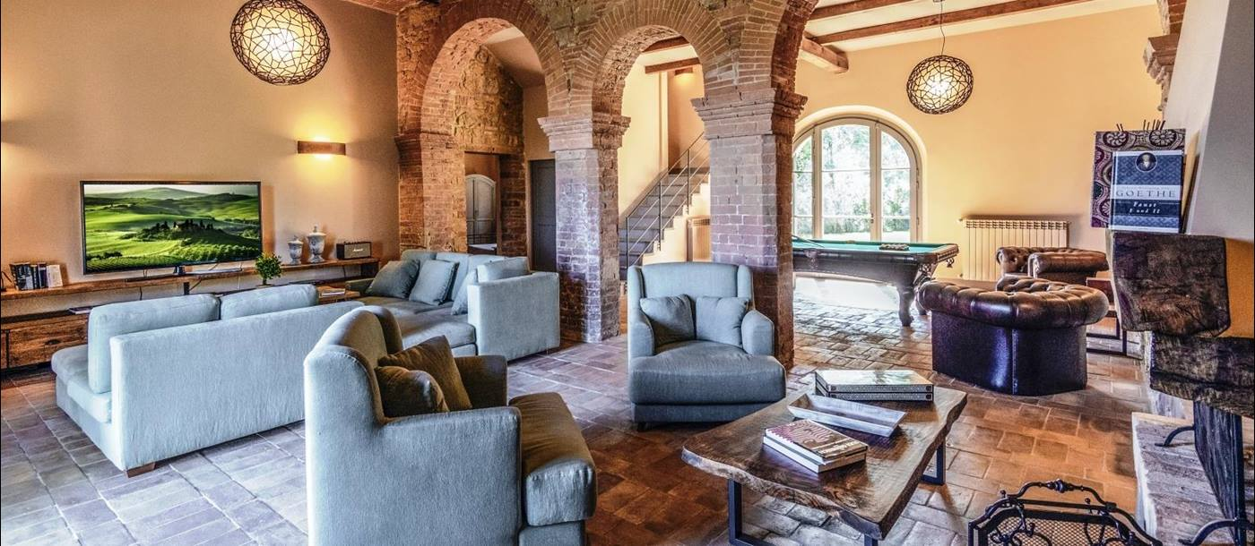 Living room with sofas, armchairs, stone archways, lights, TV and pool table at Villa del Cacciatore in Tuscany, Italy