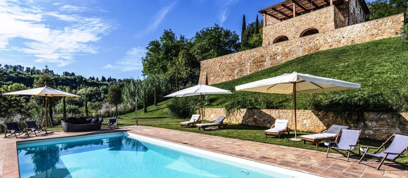 Pool area with sun loungers, umbrellas, sofa, grass, trees and view of villa at Villa del Cacciatore in Tuscany, Italy