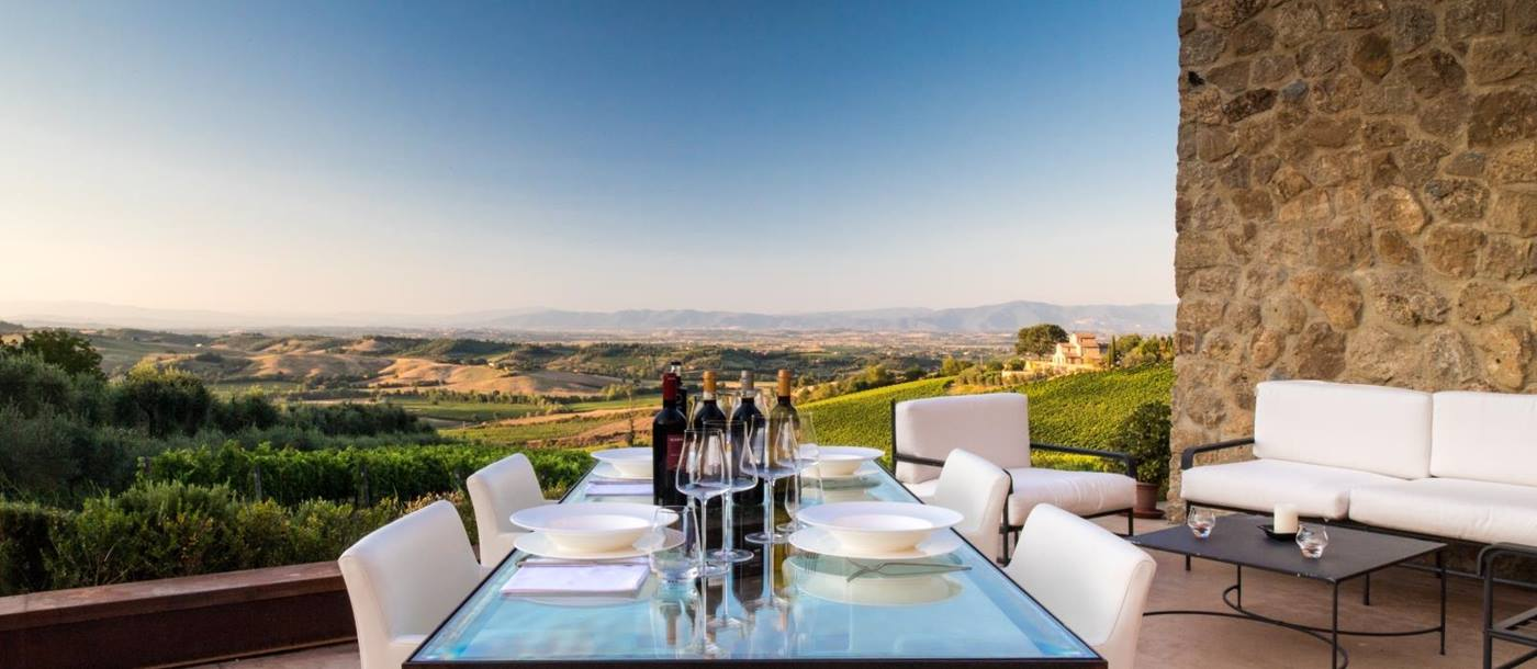 Terrace with dining table, wine, coffee table, sofas and countryside view at Villa dell'Angelo in Tuscany, Italy