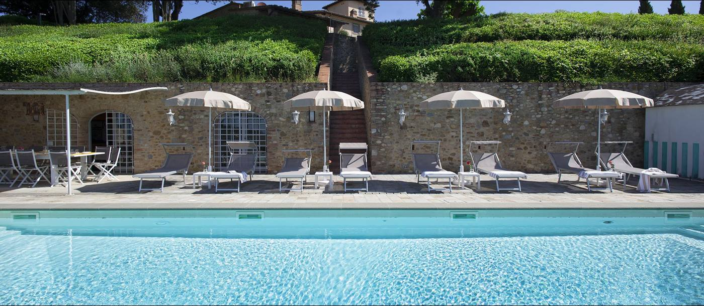 a view of the pool and sunbeds
