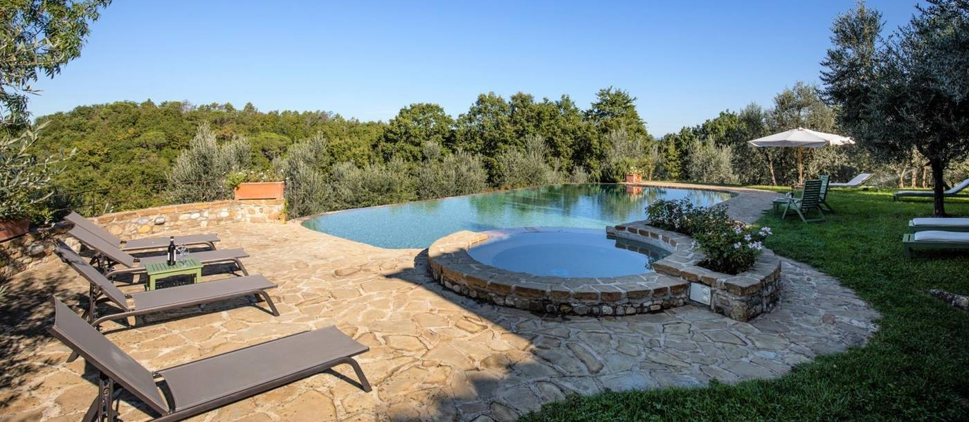 Patio next to pool with sun loungers, table, wine, umbrella and countryside view at Villa Giuliana in Tuscany, Italy