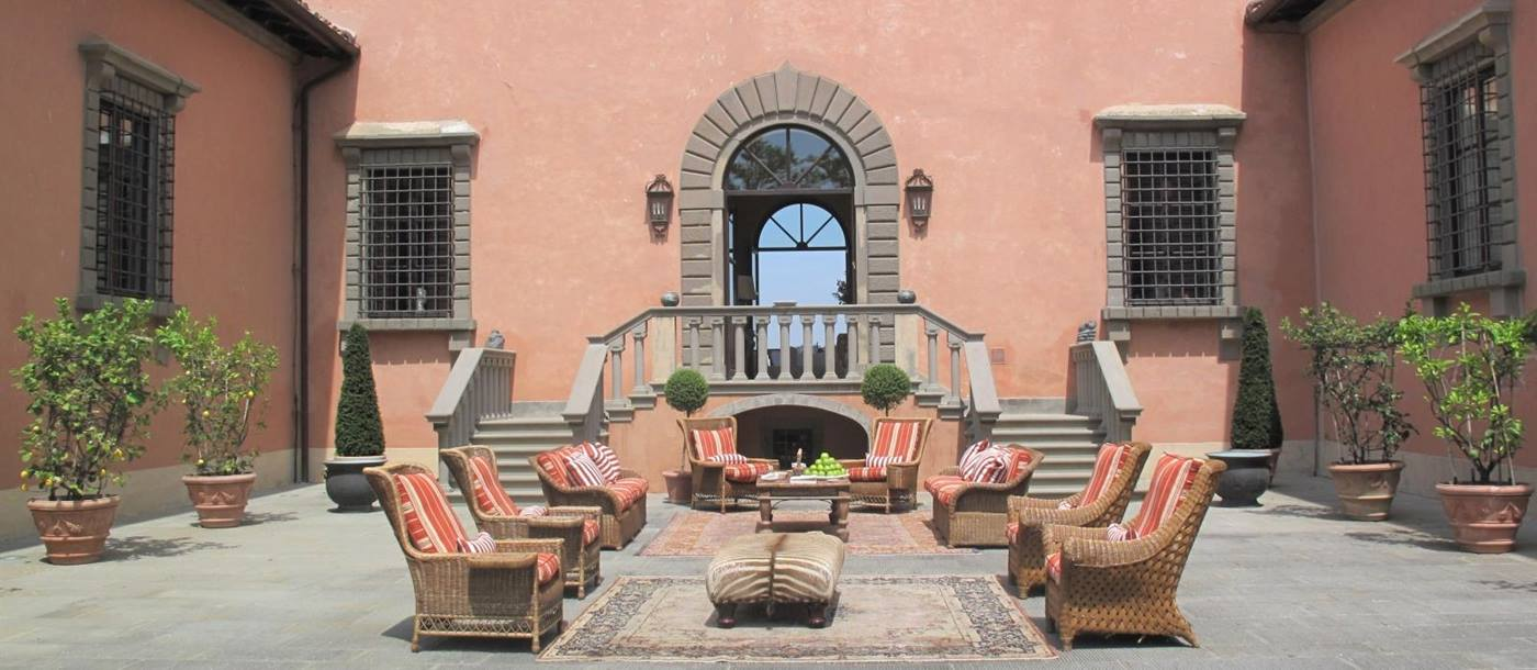 Courtyard with comfy chairs, citrus trees and stone stairs at Villa Machiavelli in Tuscany, Italy