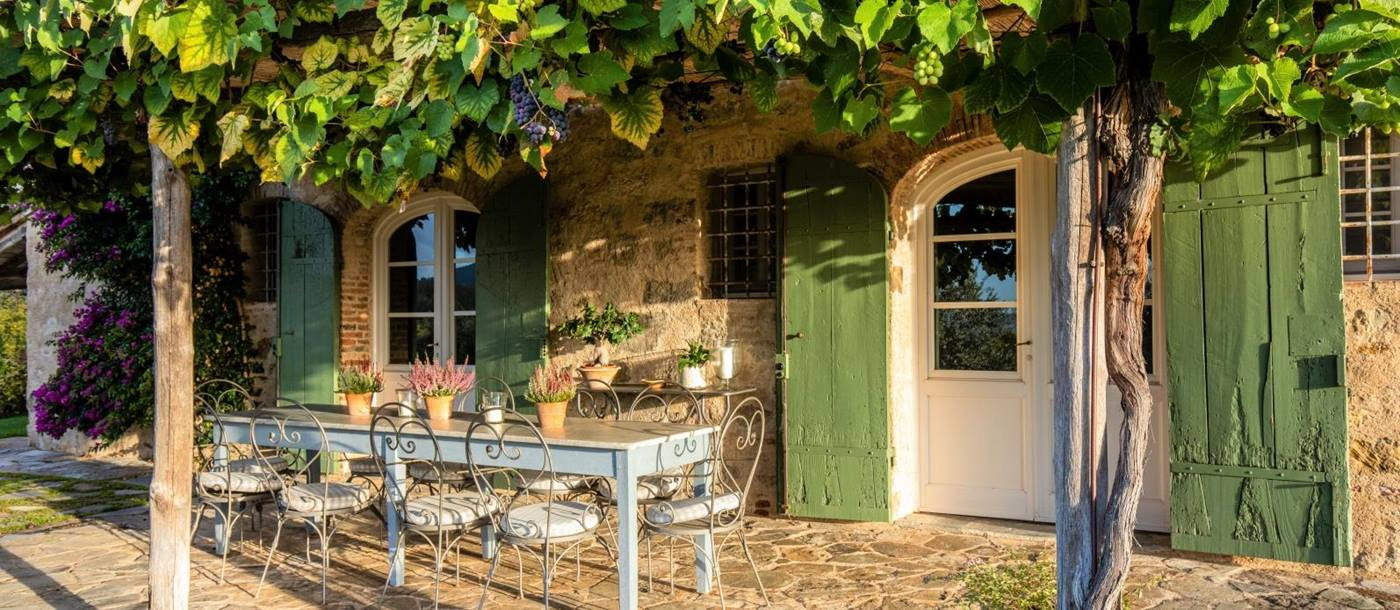 Outdoor dining area with long table, chairs, flowers and vines with grapes at Villa Ortensia in Tuscany, Italy