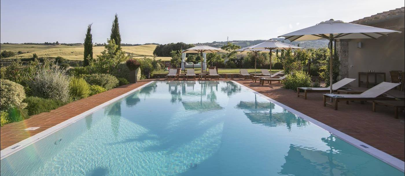A lengthways view of the pool at Villa Papavero with hills and fields of Tuscany in the background